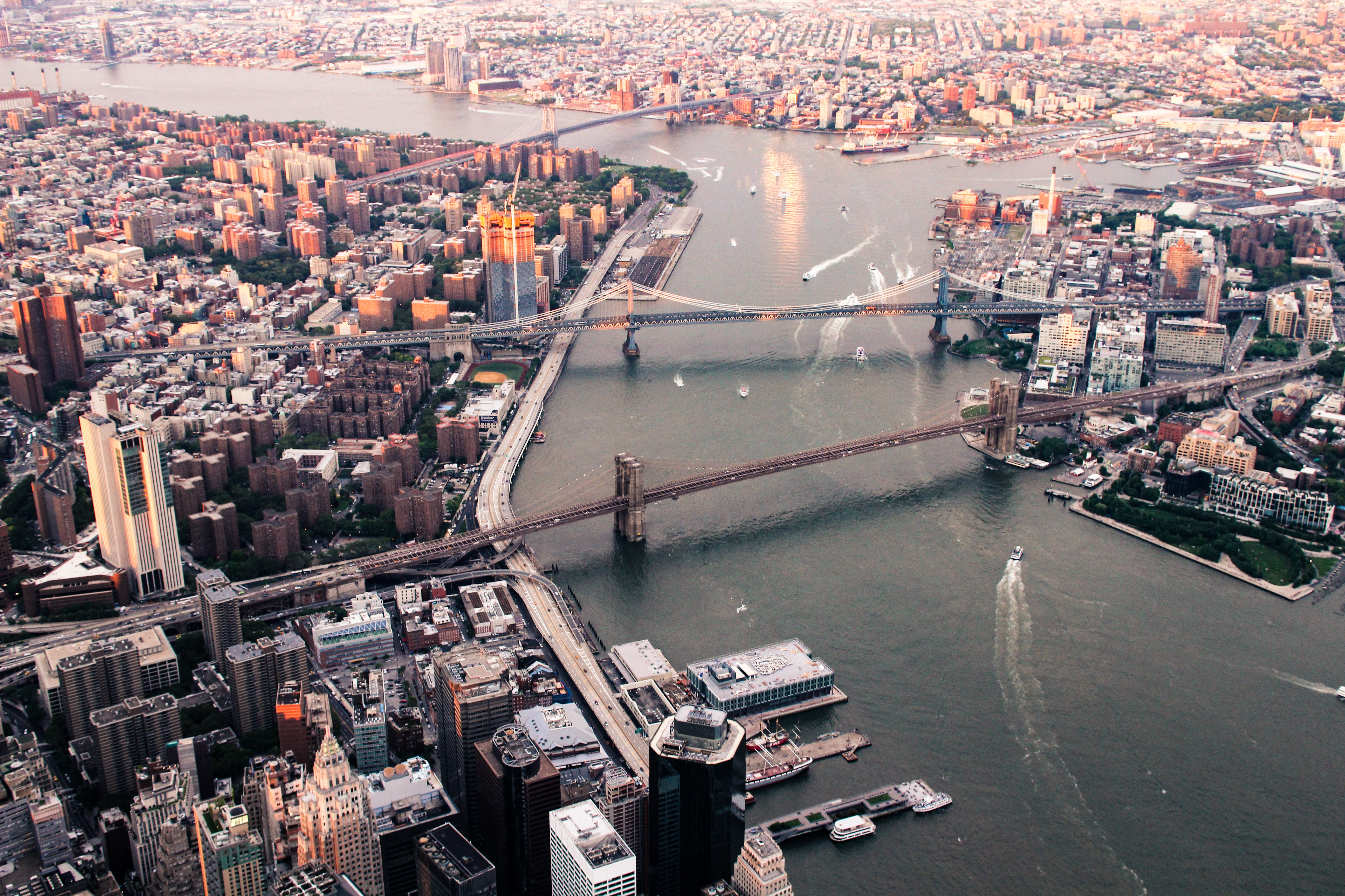A view of lower Manhattan and three East River Bridges. Many of the most affordable, popular NYC neighborhoods are in the outer boroughs